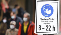 A sign with the inscription 'Masks Required. Cover your mouth and nose! 8 - 22 h' is attached to a pole on a shopping road in Frankfurt, Germany, Wednesday, Oct. 28, 2020. In order to contain the Corona pandemic, the federal and state governments are discussing further restrictions. (Arne Dedert/dpa via AP)