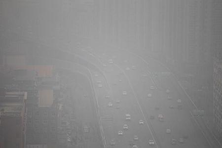 Vehicles drive on a highway amid smog in Zhengzhou