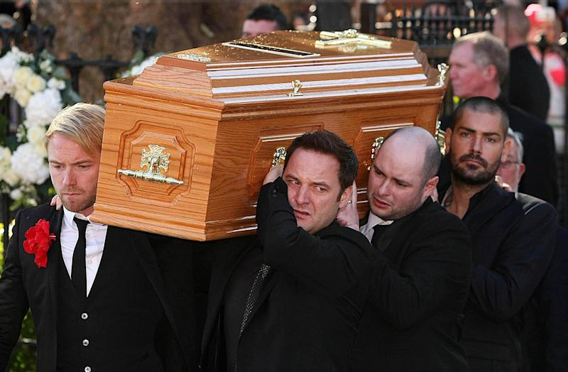 Boyzone members Ronan Keating (front left), Mikey Graham (front right) and Shane Lynch (back right) carry the coffin of Stephen Gately outside St Laurence O'Toole Church in Dublin where his funeral has been taking place. (Photo by Julien Behal/PA Images via Getty Images)