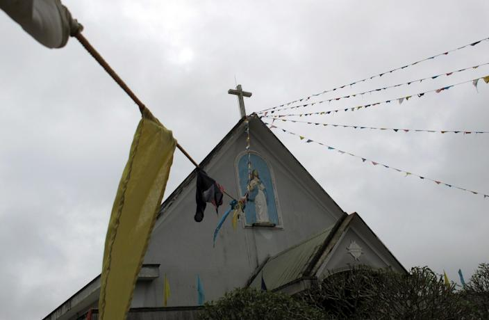 In this Thursday, Sept. 26, 2013 photo, colorful banners decorate the facade of a Roman Catholic church in Pleiku in the Vietnamese central highland province of Gia Lai. Communist Vietnam allows state-sanctioned faiths to grow, but continues to keep a close watch on all religious institutions. (AP Photo/Chris Brummitt)