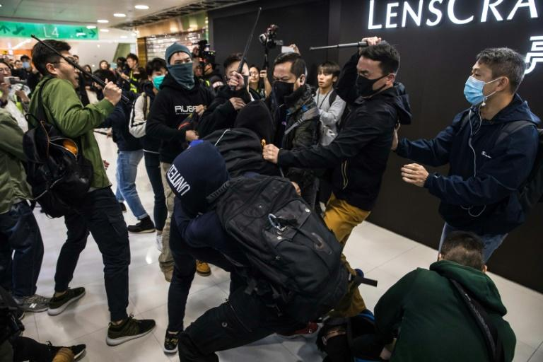 Plainclothes police, with batons, clash with pro-democracy protesters at a Hong Kong shopping mall