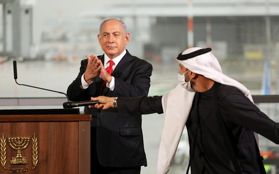 Israeli Prime Minister Benjamin Netanyahu gestures during a welcoming ceremony upon the landing of a United Arab Emirates airline flydubai flight at Tel Aviv - Pool/Reuters