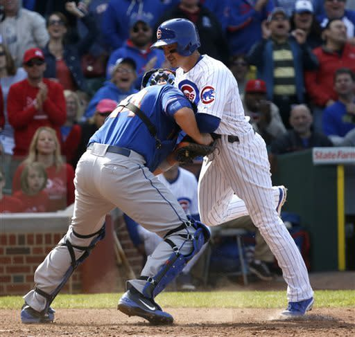 New York Mets catcher John Buck, left, tags out Chicago Cubs' Darwin Barney at home off a throw from right fielder Marlon Byrd during the eighth inning of a baseball game Friday, May 17 2013, in Chicago. Barney was advancing off a single by David DeJesus. (AP Photo/Charles Rex Arbogast)