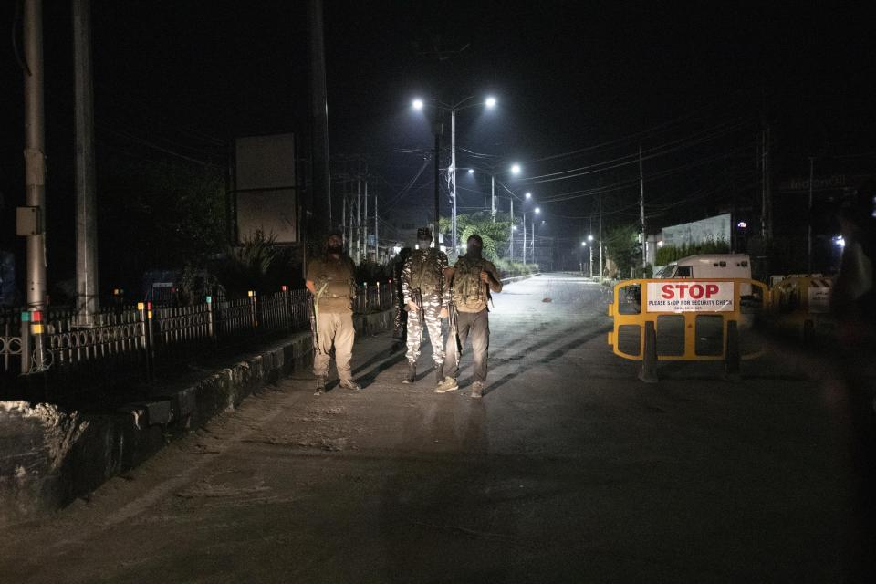 Indian policemen and paramilitary soldiers keep guard as they impose restrictions outside the residence of top separatist leader Syed Ali Shah Geelani in Srinagar, Indian controlled Kashmir, Thursday, Sept. 2, 2021. Geelani, an icon of disputed Kashmir's resistance against Indian rule and a top separatist leader who became the emblem of the region's defiance against New Delhi, died late Wednesday. He was 92. (AP Photo/Mukhtar Khan)