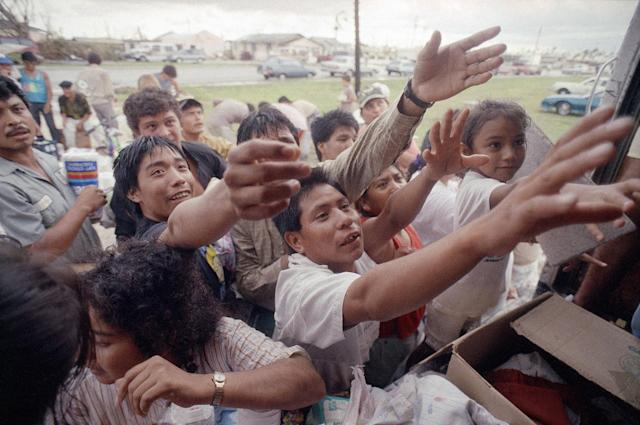 <p>Migrant workers reach for supplies of food and clothing distributed from the back of a truck in Florida City, Fla., Aug. 27, 1992. The items were donated by citizens of Key West. The workers live in an area devastated by Hurricane Andrew. (AP Photo/David Bruneau) </p>