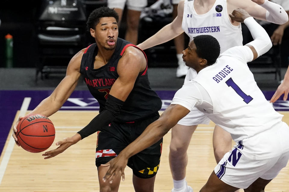 Maryland guard Aaron Wiggins, left, looks to pass as Northwestern guard Chase Audige guards during the first half of an NCAA college basketball game in Evanston, Ill., Wednesday, March 3, 2021. (AP Photo/Nam Y. Huh)
