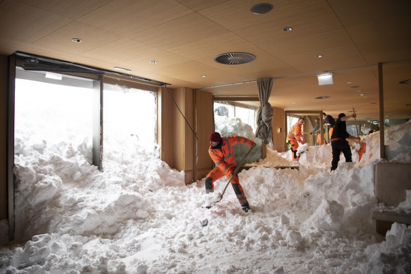 People clear snow from inside the Hotel Saentis in Schwaegalp, Switzerland,, Switzerland, Friday Jan. 11, 2019, after an avalanche. Police said three people were slightly hurt when the avalanche hit the hotel at Schwaegalp on Thursday afternoon. (Gian Ehrenzeller/Keystone via AP)