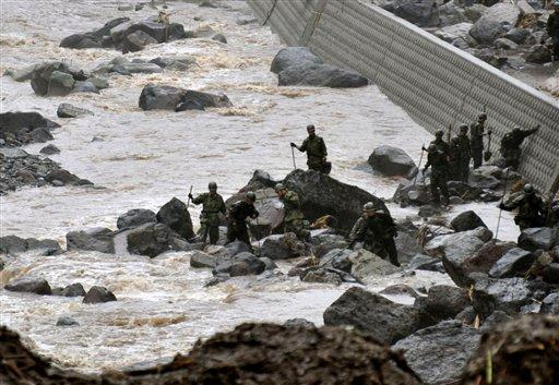 Japan's Self Defense Force members search for missing residents in the rain, in Takeda, Oita Prefecture, Japan, Friday, July 13, 2012. Heavy rains hit southern Japan, triggering flashfloods, mudslides and destroying dozens of homes. (AP Photo/Kyodo News)