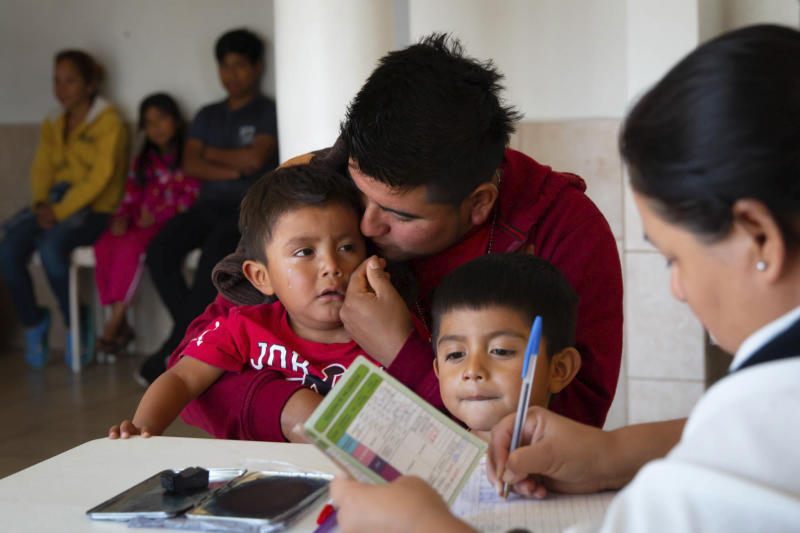 In this Jan. 28, 2020 photo provided by Cronkite News, Arizona State University, Agustin Reyes of Guererro, Mexico, wipes tears from 3-year-old Edgar Reyes at Casa del Migrante before receiving shots and medical care in San Luis Rio Colorado, Mexico. One Hundred Angels, a Phoenix organization that provides medical care and other services to migrants, helped coordinate the one-day vaccination clinic at Casa del Migrante, working with the Mexican Red Cross. (Delia Johnson/Cronkite News, Arizona State University via AP)
