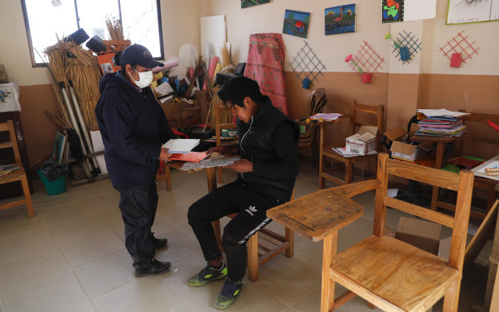Instructor Marina Vasquez and student Jose Choque go over his homework at the local school in the Urus del Lago Poopo indigenous community, in Punaca, Bolivia, Monday, May 24, 2021. Aided by the government and a local foundation, community elders have invited teachers from a related branch of the Uru, to teach their native tongue — one of 36 officially recognized Bolivian languages — to their children. (AP Photo/Juan Karita)