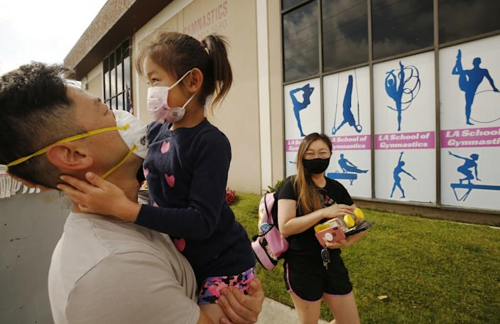 "Shawn Chou and Jennifer Lee drop off their daughter Samantha Chou, 6, at L.A. Gymnastics in Culver City. They are among parents who have pinned their hope on summer camps reopening. <span class=""copyright"">(Al Seib / Los Angeles Times)</span>"