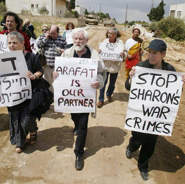 In this file photo taken on April 22, 2002, Gush Shalom peace activists, including group founder Uri Avneri (C), march towards the headquarters of Palestinian Authority president Yasser Arafat in the Israeli-occupied West Bank city of Ramallah