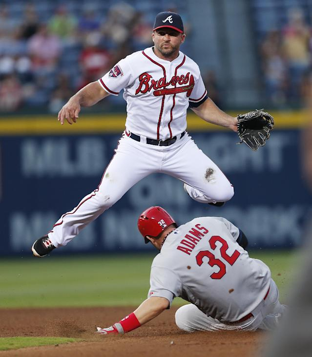 Atlanta Braves second baseman Dan Uggla (26) avoids St. Louis Cardinals' Matt Adams (32) as he turns double play on a Jhonny Peralta (27) ground ball in the fourth inning of a baseball game, Tuesday, May 6, 2014, in Atlanta. (AP Photo/John Bazemore)