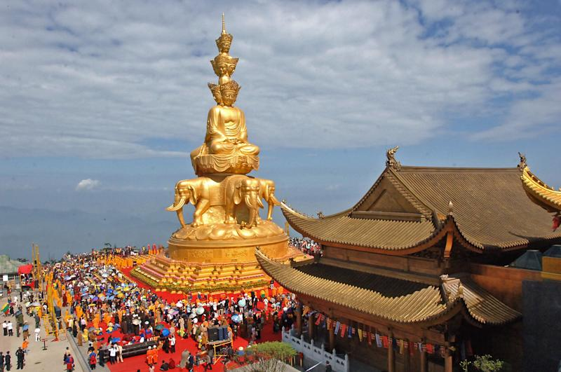 In this photo taken June 18, 2006, worshippers attend a ceremony at the Jin Ding, or Golden Tip, on Emei Mountains in Emeishan city in southwest China's Sichuan province. Authorities announced Monday, Oct. 22, 2012, a ban on temples selling shares to investors after leaders of several temples planned to pursue stock market listings for them as commercial entities. (AP Photo) CHINA OUT