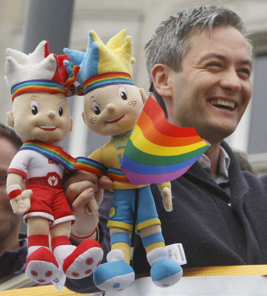 Polish lawmaker Robert Biedron holds Euro 2012 soccer championships mascots covered with a multicolor flag during the gay parade in Warsaw, Poland, Saturday, June 2, 2012. Gay rights activists held the parade as gays become increasingly visible in this conservative mostly Catholic country but still face significant prejudice. (AP Photo/Czarek Sokolowski)