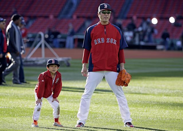 Boston Red Sox's Koji Uehara, of Japan, warms up with his son Kazuma before Game 2 of baseball's World Series Thursday, Oct. 24, 2013, in Boston. (AP Photo/David J. Phillip)