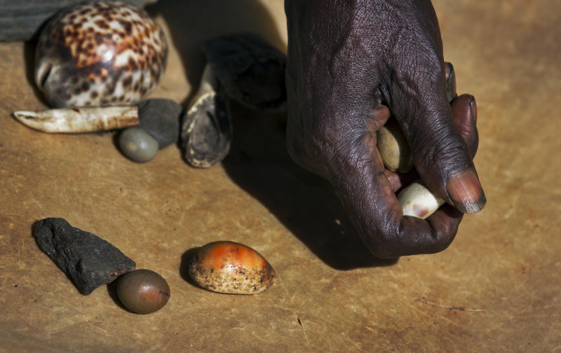 Kenyan witch-doctor John Dimo, who claims to be 105 years old, throws shells, bones, and other magic items to predict the outcome of the U.S. election, in front of his hut in the village of Kogelo, from where President Barack Obama's late father came from and whom Dimo claims to have known, in western Kenya Monday, Nov. 5, 2012. While pollsters in the U.S. are using armies of live-interviewers, statistical analysis and the latest automated polling technology, Dimo, who inherited the work from his father in 1962 and has two wives and five children, is confident of his traditional methods and claimed the result would go in Obama's favor. (AP Photo/Ben Curtis)