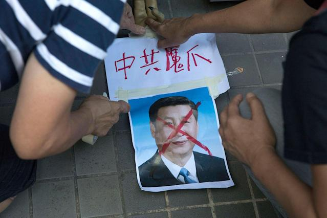 "<p>Pro-democracy activists paste the words ""Chinese Communist Demon Claws"" on a defaced photo of Chinese President Xi Jinping before attempting to march in protest towards the venue where official ceremonies are held to mark the 20th anniversary of Chinese rule over Hong Kong in Hong Kong, Saturday, July 1, 2017. (Photo: Ng Han Guan/AP) </p>"