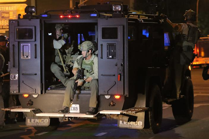"""Kentucky State Police officers ride in an armored truck as it drives down West Jefferson Street in Louisville. <p class=""""copyright"""">Daniel Shular</p>"""