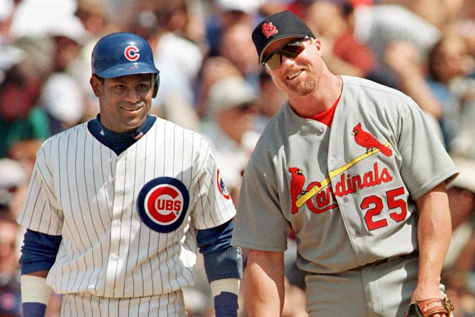 The Chicago Cubs' Sammy Sosa stands with St. Louis Cardinal's first baseman Mark McGwire between pitches after Sosa singled in the second inning 28 May, 1999, at Wrigley Field in Chicago, Illinois. It was the first time the pair had played each other since last year's home run race. The Cubs won 6-3 with help from a home run from Sosa.    AFP PHOTO/John ZICH (Photo by JOHN ZICH / AFP)        (Photo credit should read JOHN ZICH/AFP via Getty Images)