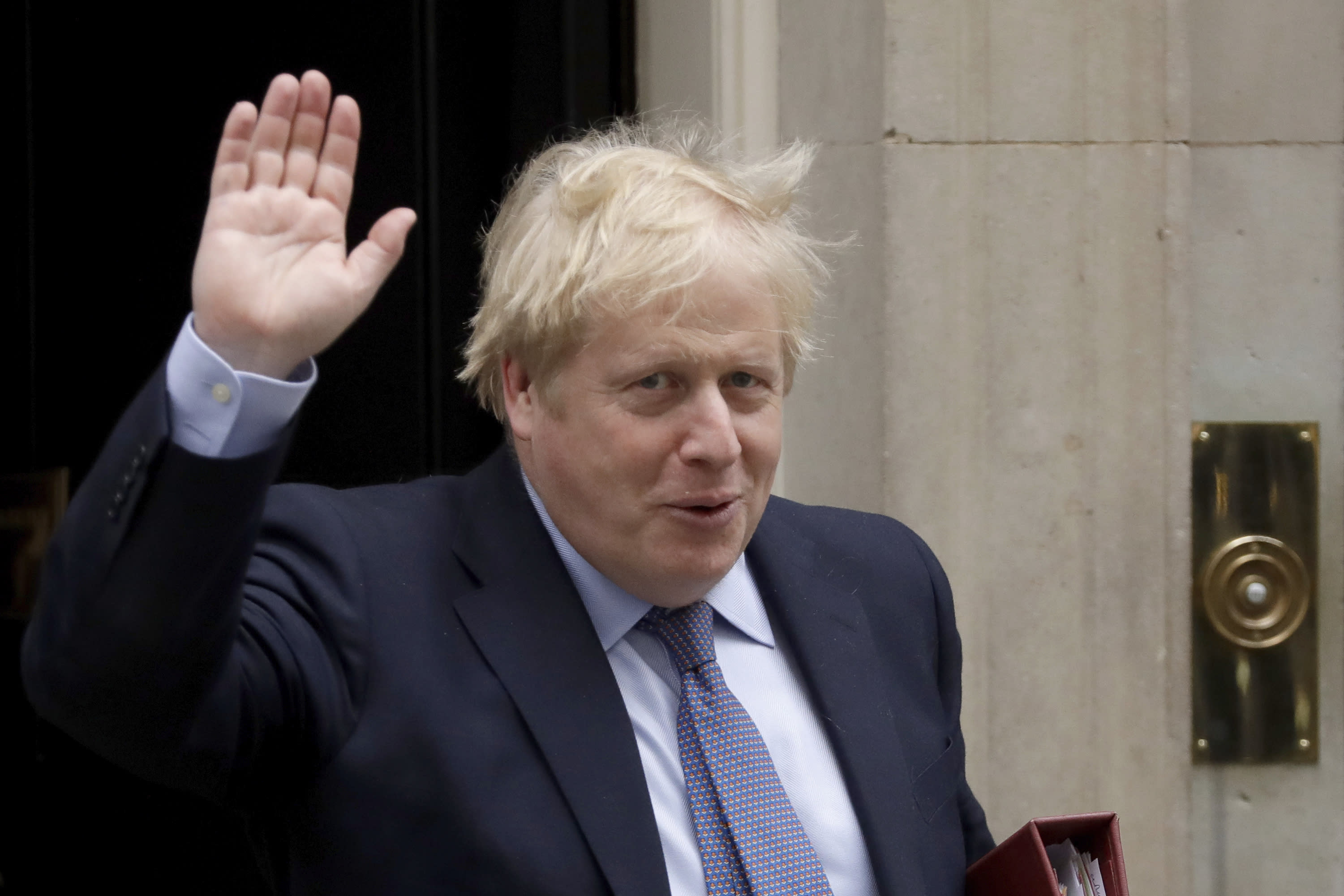 British Prime Minister Boris Johnson waves at the media as he leaves 10 Downing Street in London, to attend the weekly Prime Minister's Questions at the Houses of Parliament, in London, Wednesday, Feb. 26, 2020. (AP Photo/Matt Dunham)