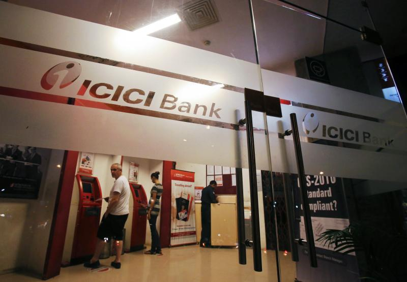 Customers use ATM machines at an ICICI Bank branch in Mumbai