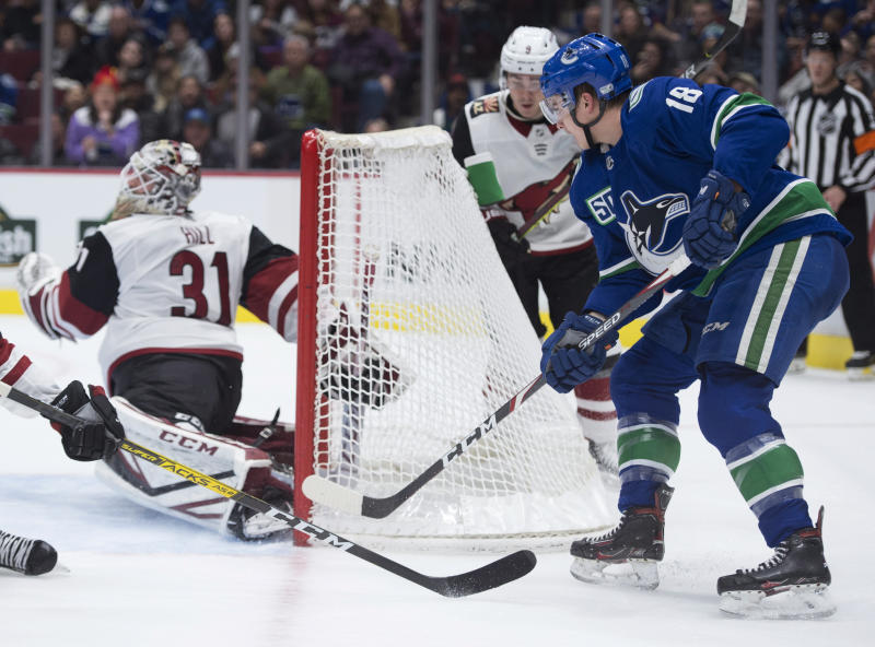 Vancouver Canucks right wing Jake Virtanen (18) slips a shot past Arizona Coyotes goaltender Adin Hill (31) for a goal during the second period of an NHL hockey game Thursday, Jan. 16, 2020, in Vancouver, British Columbia. (Jonathan Hayward/The Canadian Press via AP)