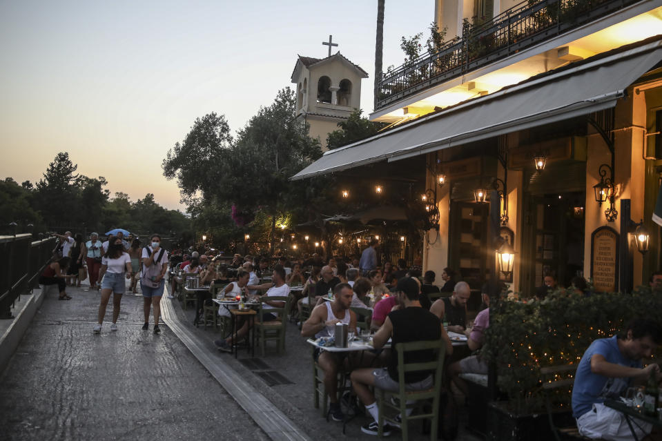 People sit at a restaurant in the Plaka district of Athens on Friday July 16, 2021. Greece became the latest on Friday, with a new measure coming into effect requiring proof of vaccination or recent recovery from COVID-19 for access to indoor restaurants, cafes, bars and movie theaters. Children can enter with negative tests. (AP Photo/Petros Giannakouris)