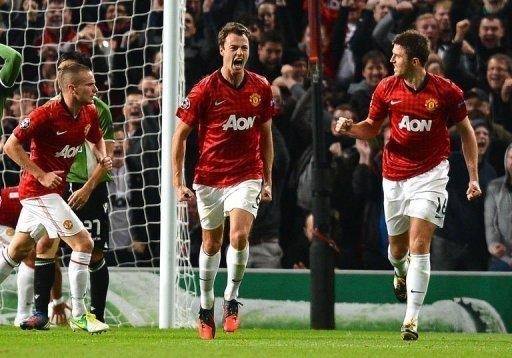 Manchester United's Northern Irish defender Jonny Evans (C) celebrates with teammate English midfielder Michael Carrick (R) after scoring his team's second goal during the UEFA Champions League group H football match between Manchester United and Braga at Old Trafford in Manchester. United won 3-2