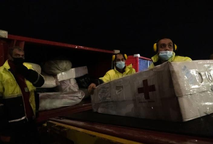 Workers unload a shipment of humanitarian aid from a plane arriving from Russia at Zvartnots airport outside Yerevan