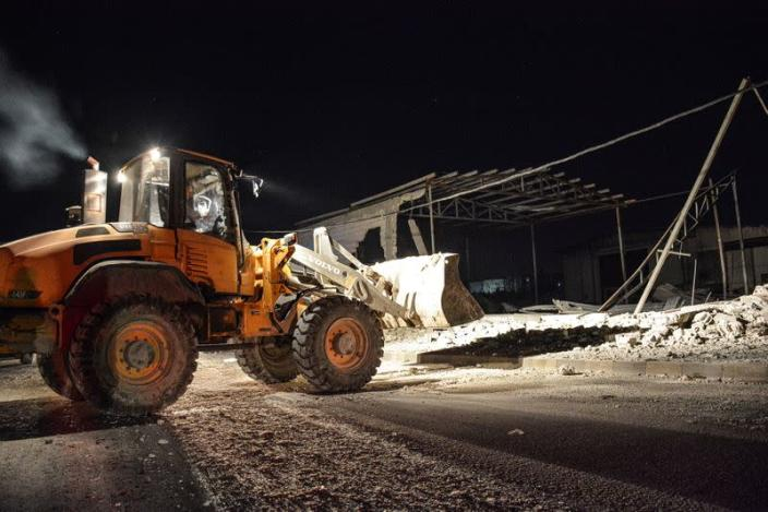A man operates a front loader at a site after pre-dawn raids on the Mediterranean port region of Latakia