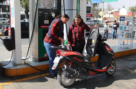 An employee fills a scooter's tank with fuel at a petrol station in Tula, Mexico, January 11, 2019. REUTERS/Mohammed Salem