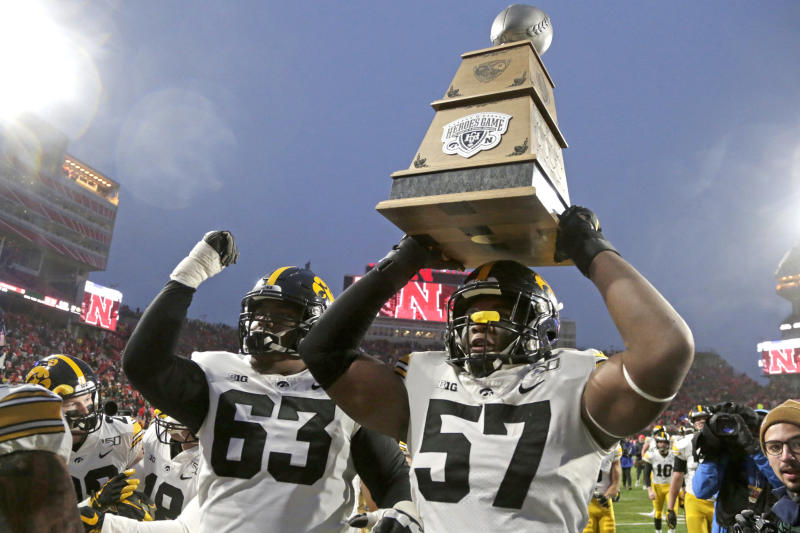 Iowa defensive end Chauncey Golston (57), with offensive lineman Justin Britt (63), carries the Heroes Game Trophy following an NCAA college football game against Nebraska in Lincoln, Neb., Friday, Nov. 29, 2019. Iowa won 27-24. (AP Photo/Nati Harnik)