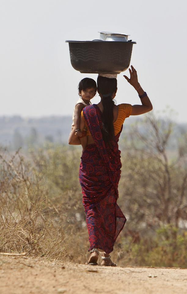 <p>An Indian woman carries her child and balances her utensils on her head as she walks to work in a field on a hot summer day, outskirts of Hyderabad, India, Tuesday, March 21, 2017. (AP Photo /Mahesh Kumar A.) </p>