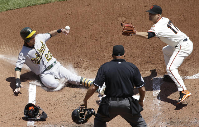 Oakland Athletics' Josh Reddick (22) slides into home to score against San Francisco Giants pitcher Tim Hudson (17) as umpire Kerwin Danley, bottom, watches during the second inning of a baseball game in San Francisco, Sunday, July 26, 2015. (AP Photo/Jeff Chiu)