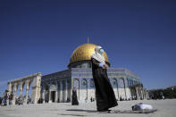 A Muslim woman takes part in Friday prayers at the Dome of the Rock Mosque in the Al Aqsa Mosque complex in the Old City of Jerusalem, which has reopened to visitors following a third lockdown to curb the spread of the coronavirus, Friday, Feb. 12, 2021. (AP Photo/Mahmoud Illean)