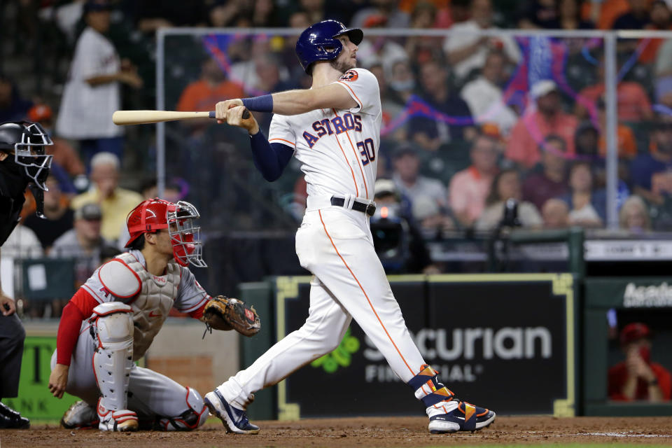 Houston Astros' Kyle Tucker (30) watches his home run in front of Los Angeles Angels catcher Kurt Suzuki, left, during the fifth inning of a baseball game Tuesday, May 11, 2021, in Houston. (AP Photo/Michael Wyke)