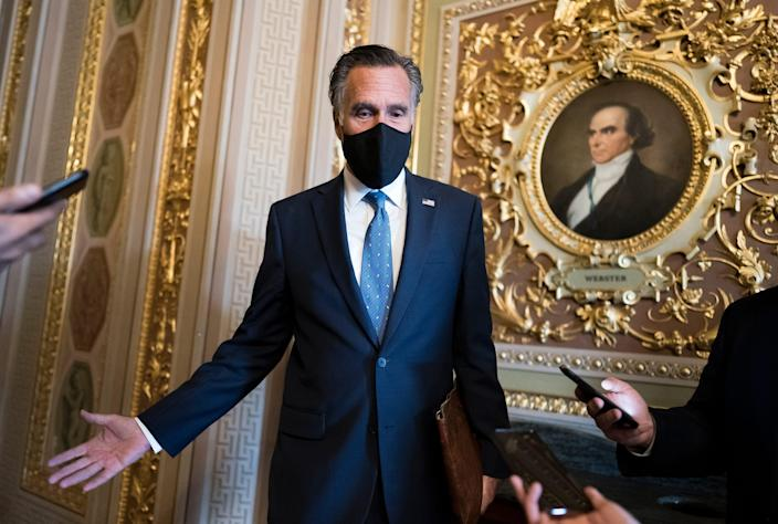 Sen. Mitt Romney, R-Utah, pauses to answer questions from reporters as senators arrive to vote on President Joe Biden's nominee for United Nation's ambassador, Linda Thomas-Greenfield, at the Capitol in Washington, Tuesday, Feb. 23, 2021. (AP Photo/J. Scott Applewhite) ORG XMIT: DCSA135