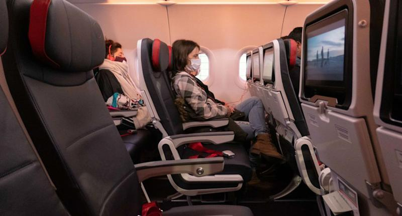 Pictured is a woman sitting on a plane wearing a face mask.