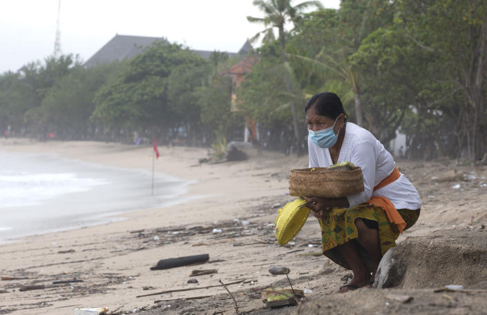 A Balinese woman gives an offering to Hindu god in Bali, Indonesia on Wednesday, Feb. 3, 2021. Airlines and hotels are desperately holding out for a recovery in travel. But instead they're seeing more restrictions, from Canada to Indonesia. Governments are extra cautious due to the new, more contagious variants of the coronavirus. (AP Photo/Firdia Lisnawati)