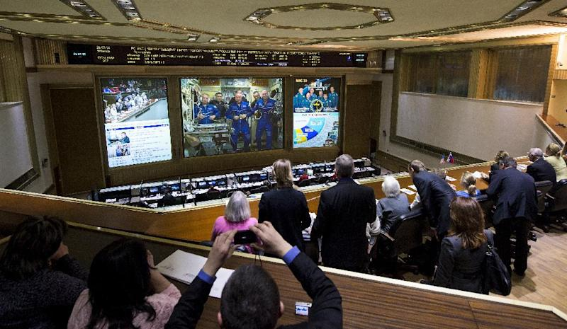 A view from the balcony of the Russian Mission Control Center shows live television of the Expedition 39 crew members gathered together on the International Space Station a few hours after the Soyuz TMA-12M spacecraft docked on Friday, March 28, 2014, in Korolev, Russia. Expedition 39's arrival to the International Space Station comes two days after they launched from the Baikonur Cosmodrome in Kazakhstan. (AP Photo/NASA, Joel Kowsky)