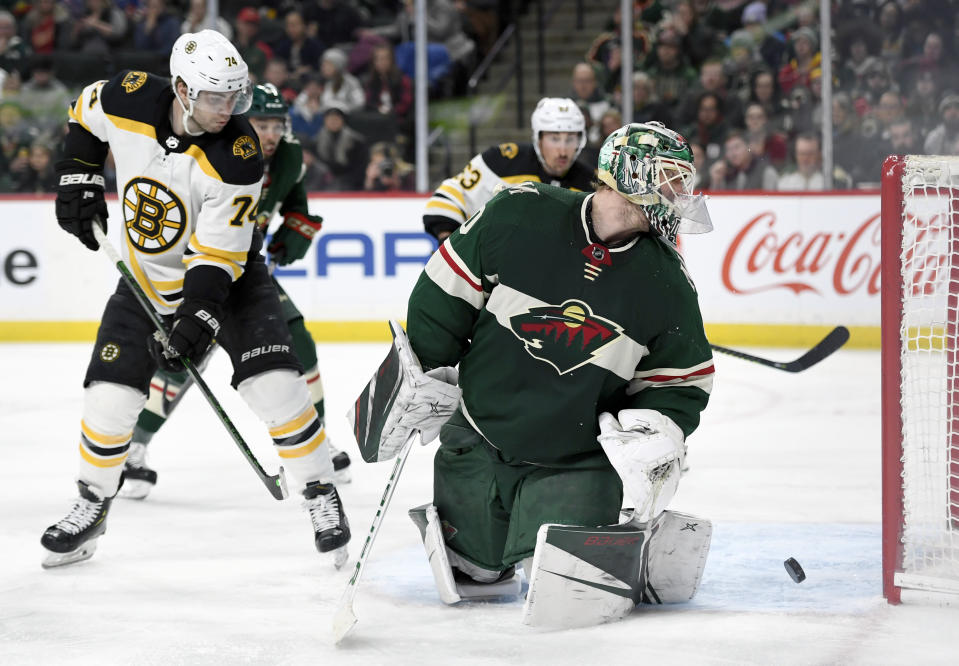 Minnesota Wild goaltender Devan Dubnyk (40) and Boston Bruins left wing Jake DeBrusk (74) watch as the shot by Boston Bruins' Torey Krug, not pictured, goes into the net during the second period of an NHL hockey game Saturday, Feb. 1, 2020, in St. Paul, Minn. (AP Photo/Hannah Foslien)