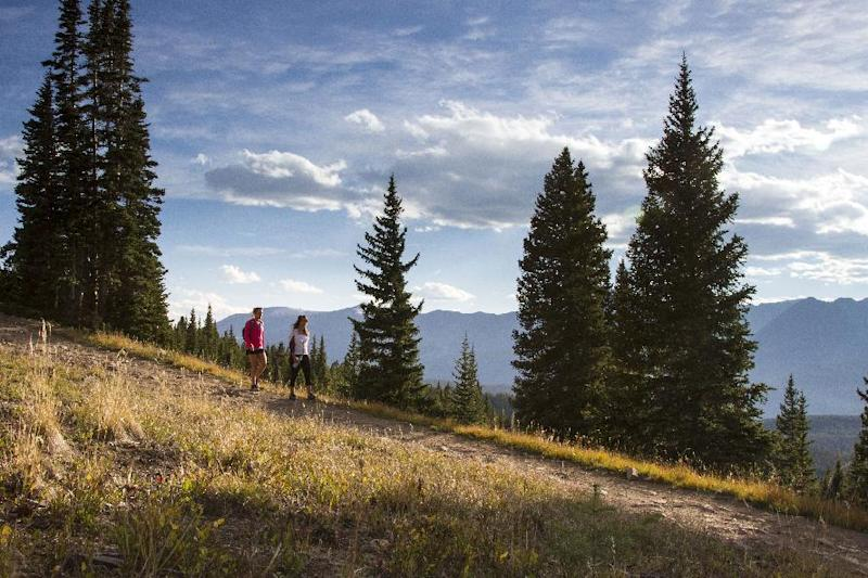 This 2012 photo provided by GoBreck shows hikers on a hilly trail in Breckenridge, Colo. Breckenridge may be best known as a ski resort but it offers many summer and fall activities for visitors, along with offseason deals. (AP Photo/GoBreck, Liam Doran)