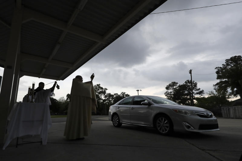 Fr. Steve Buno, Pastor of St. Rita of Cascia Catholic Church in Harahan, La., performs drive-thru Benediction of the Blessed Sacrament, as a form of social distancing due to the new coronavirus, during Holy Week, Tuesday, April 7, 2020. (AP Photo/Gerald Herbert)