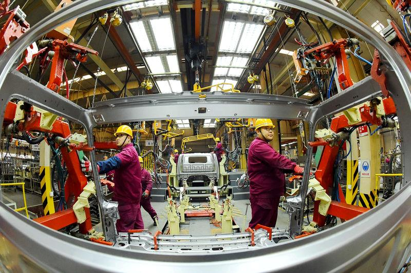 Employees work on a production line manufacturing light trucks at a JAC Motors plant in Weifang