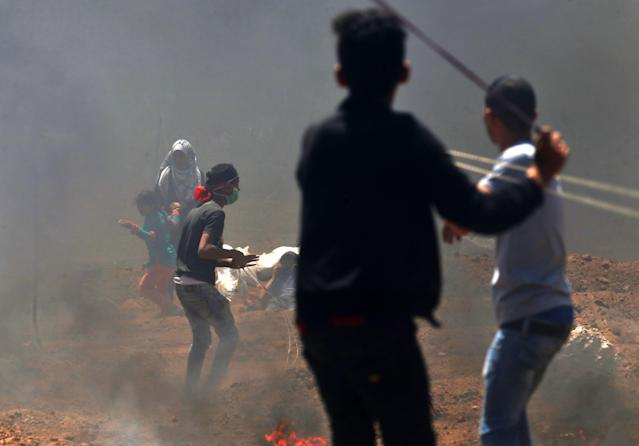 <p>Palestinian children use slingshots during clashes with Israeli forces near the border between Israel and the Gaza Strip on May 14, 2018. (Photo: Mohammed Abed/AFP/Getty Images) </p>