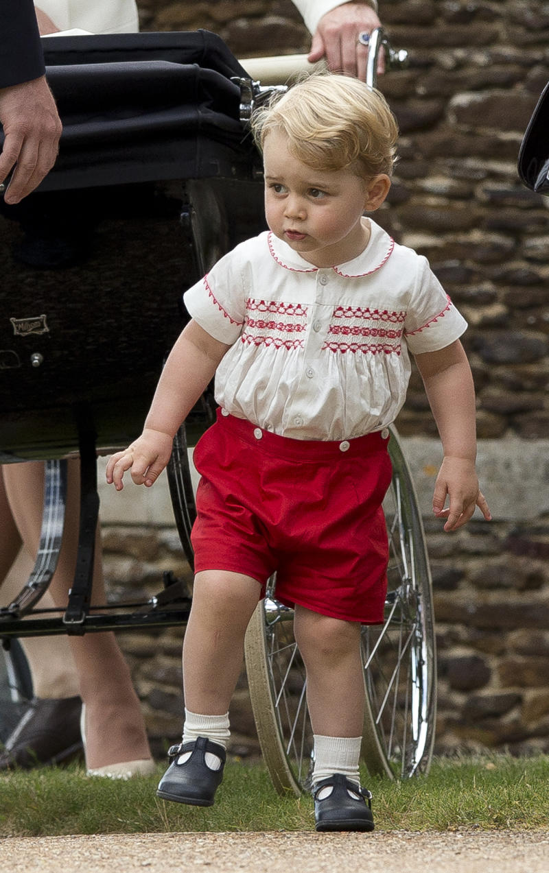 KING'S LYNN, ENGLAND - JULY 05: Prince George of Cambridge stands near Princess Charlotte of Cambridge's pram at the Church of St Mary Magdalene on the Sandringham Estate after the Christening of Princess Charlotte of Cambridge on July 5, 2015 in King's Lynn, England. (Photo by Matt Dunham - WPA Pool/Getty Images)