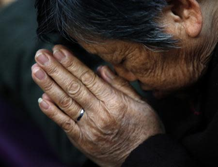 A believer prays during a weekend mass at an underground Catholic church in Tianjin in this November 10, 2013. REUTERS/Kim Kyung-Hoon