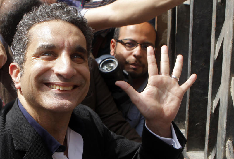 File -- In this Sunday, March 31, 2013 file photo, Egyptian television satirist Bassem Youssef — known as Egypt's Jon Stewart —waves to his supporters as he enters Egypt's state prosecutors office to face charges  for allegedly insulting Islam and the country's leader, in Cairo, Egypt. A Cairo court turned down on Saturday, April 5, 2013, a separate suit filed by a Muslim Brotherhood lawyer demanding that a popular Egyptian satirist's TV show be banned for allegedly insulting the president and excessive sexual innuendo.  There have been multiple complaints filed in courts and to state prosecutors by Islamist lawyers against Youssef and other public figures for their political or religious opinions. (AP Photo/Amr Nabil, File)