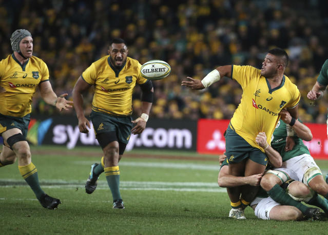 Australia's Brandon Paenga-Amosa, right, passes back as he is tackled by Ireland during their rugby union test match in Sydney, Saturday, June 23, 2018. (AP Photo/Rick Rycroft)